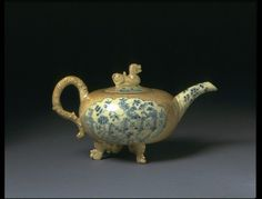 Teapot | Booth, Enoch | V&A Place of origin: Staffordshire, England (made)  Date: ca. 1745 (made)  Artist/Maker: Booth, Enoch (probably, maker)  Materials and Techniques: Buff or cream earthenware, decorated with underglaze manganese purple and cobalt blue