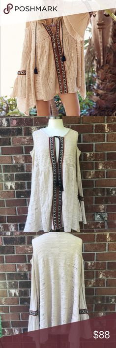 Free People For the Love of Flowers Top Excellent condition Gauzy crochet tribal inspired open shoulder tunic featuring embroidery detailing. Low V-Neck with drawstring ties and tassel ends. Effortless, oversized fit with bell sleeves and an uneven hem.  Free People  19% Nylon 81% Cotton Hand Wash Cold Import * inner tag cut to prevent store returns Free People Tops