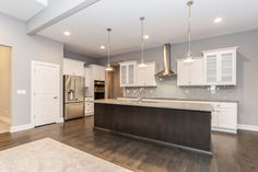 Two-tone custom kitchen design with light painted outer cabinets and dark stained center island with stainless steel appliances and custom subway tile backsplash.