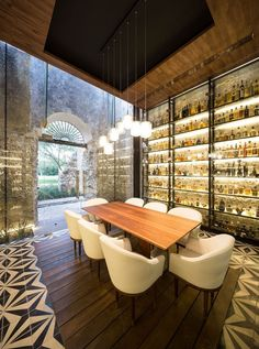 This modern restaurant inside a renovated farm building has a private dining room for small gatherings. Walls of backlit shelves highlight the various bottles on display.