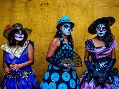 Three young women sport ghoulish, indigo grins to celebrate the dead for Día de los Muertos, or Day of the Dead. The holiday is a celebratory and sometimes emotional way to remember those who have died. Traditions include trails of marigold petals leading souls from the street to the family home, egg-based pan de muerto, and graveside picnics. The best known ceremonies are located on Mexico's tiny island of Janitzio and in towns like Xoxo outside of Oaxaca city.