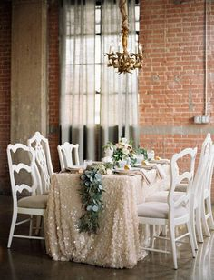 Accessorize your wedding table for the winter with glam gold sequined tablecloths.