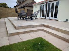 A large contemporary patio terrace using sawn mint sandstone with uplighters and slatted trellis, designed and built by SilverBirch Gardens Ltd