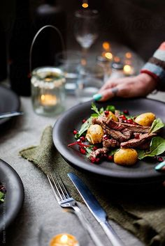 Delicious rib eye steak salad with saute potato and pomegranate seeds. by Darren Muir for Stocksy United