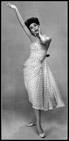 Simone in fabulous cocktail dress of black on white polka-dotted chiffon, the strapless dress is draped and gathered back by black ribbon where it falls in floating panels, by Balmain, photo by Pottier, 1958