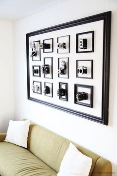 A collection of 12 vintage camera's inside frames, which are surrounded by one big frame by Jurg Roessen.