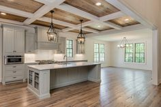 Beautiful Kitchen with grey cabinetry and island.  Love the coffered ceilings and the lantern light fixtures over the island with breakfast bar.  The stain of the hardwood floors is very pretty, too, and compliments the color of the walls and cabinets. #Kitchen #KitchenDesign #KitchenIdeas