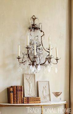 An antique sconce glistens above an antique demilune table. - Photo: Werner Straube / Design: Gail Plechaty