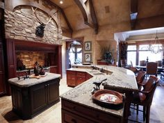 This rustic Iowa mansion pairs stone and wood in this stunning kitchen with dark wood cabinets and custom details, including wooden arches and intricate door trim. It creates an old-world, lodge feel with modern amenities and comfort. Wooden Arch, Dark Wood Cabinets, Buy Photos, Door Trims, Cottage Homes, Old World, Dining Area, Iowa, Rustic