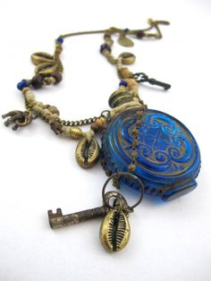 'Bygone Blue' Exclusive one-off antique piece handcrafted in our Byron Bay studio.  Antique royal blue embossed glass perfume bottle from India circa 1890s.  Antique keys from France and India.  Solid brass cowry shell pendants.  Solid brass elephant charm from a Buddhist Temple in Thailand.  Small snake vertebrae trade beads from Kenya.  Antique decorative glass beading from Nepal.  Wooden and brass beading on knotted hemp and brass chain.  AUD $539  SOLD | www.republicofyou.com.au