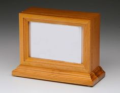 (http://www.casketsdirect.com.au/products/wooden-oak-photo-urn.html)  Photo frame wood cremation urn. Suitable for use as a small pet urn.