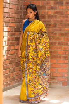 Just the most richly detailed saree ever! A lovely mustard rawsilk saree with intricately zari worked Kalamkari appliquéing in a gradual slant, which ends in the most opulent pallu with dancing Radha Krishna. And don't miss the cool border edging with blue orange diamond motifs. Endless pairing options for this drool worthy drape…Go with any color in the appliqué or border detailing and be a stand out dame!