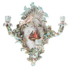 Three-branch Meissen porcelain wall light. Plaque painted with romantic park scene. Applied with flowers and angels. Crossed swords mark in blue. 19th century work. Minor chips. Right wing damaged. <br> 46 x 42 <br><br> Drie-armige muurappliek. Meissen porselein. <br> Beschilderd op plaque met romantisch koppel in park. <br> Reliëfdecor van bloempjes en engeltje. Gemerkt met gekruiste zwaarden in onderglazuurblauw. <br> 19de eeuws werk. Minieme afschilferingen. Rechtervleugel engel bes <br…