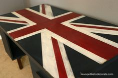 Jack – A Sophisticated Writing Desk | becauseiliketodecorate...The base is a custom mixture of Behr Midnight Dream (two coats), and the desktop Union Jack design is done with Annie Sloan Chalk Paint (ASCP) in Old White and Glidden Red Delicious. After complete, I did a light sanding with a medium grade sanding block, then finished with Annie Sloan Clear Wax (Applied with a brush and buffed smooth with a dry cloth).