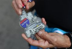 A volunteer holds the marathon finisher medals at the Annual Detroit Free Press/Talmer Bank Marathon in Detroit. Detroit Free Press, Marathon, Running, Summer, Photography, Ing Marathon, Racing, Photograph, Marathons