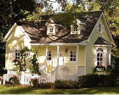Yellow and white cottage with a picket fence