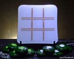 This is a (approximately square slumped fused glass tic tac toe board with 10 game pieces. It is a white glass board with gold paint in the etched grid on top. The game pieces are green wi Tic Tac Toe Board, Tic Tac Toe Game, Glass Beer Mugs, Getting Fired, Game Pieces, Gold Paint, Crafts To Sell, Fused Glass, Board Games