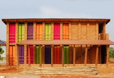 Sra Pou Vocational School in Cambodia - using sundried mud bricks from local red earth and beautiful homemade shutters.