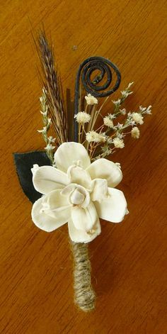 Rustic wedding boutonniere. The flower is wood! She also has some baby's breath…