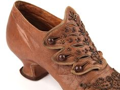 Low Louis heels tan leather pumps with high figured tongue, fixed with three pairs of buttons. French, ca. 1905-10