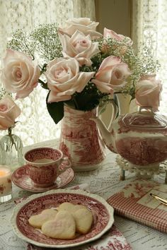 a beautiful table setting of pink Staffordshire china for further spring or christmas with a change to greenery and red berries in the water pitcher... ..
