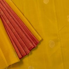 "The ""Amber Yellow"" #handwoven Kanjivaram Silk Sari from Parisera is woven with gold zari paisley motifs all over the body. A Section of Red with zari floral motifs makes up the attractive pleats. An attractive gold zari adorn the red pallu. The Red blouse completes the sari."