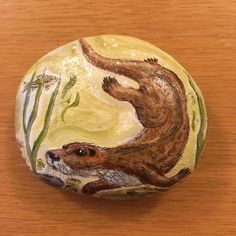 Otter painted on Devon beach stone. The idea for this originally came from The Otter pub, in the Otter valley in Devon, where a similar image was carved into the wooden front of the bar. (The second photo shows the pre-varnished version, as the varnish creates reflections when photographed).  Stone measures approx 9.5 x 8 x 2.5 cm.