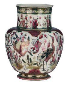 Zsolnay váza, 1883-85 között, Zsolnay Júlia munkája Porcelánfajansz, madár-és növénymotívumokkal, Magasság: 32 cm Jelzés: máz alatt kék színű irottbetűs márkajelzés, Zsolnay Pécs, TJM családi bélyegző, fazonszám: 879 Kikiáltási ár: 120 000 Ft