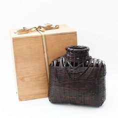 A woven bamboo ikebana (flower arranging) basket with its wooden box created by famed Japanese bamboo artist Maeda Chikubosai I (????? 1872-1950). The vase is woven from strips of bamboo stained a ...