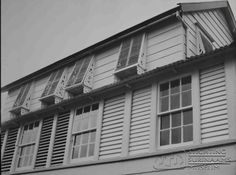 Typerend voor Nickerie zijn deze schuine shutters met opengewerkte zijkant. De verdiepingen hebben afwisselend schuiframen en shutters. Zgn. Demerara windows. Datum: Locatie: Nickerie, Suriname Vervaardiger: Inv. Nr.: 20-90 Fotoarchief Stichting Surinaams Museum