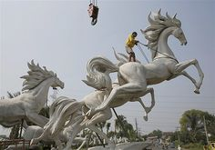 Image: A worker tightens a rope to raise a 13-foot statue of horses in Bogor, Indonesia, on Sept. 19
