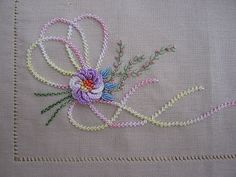 *EMBROIDERY ~ Palestrina stitch used for the 'ribbon', Raised Buttonhole stitch for the main flower, Bullions for the small flowers, Feather stitch & French Knots for the floral stems & 2 rows of alternating Back Stitch for the stems. Brazilian Embroidery Stitches, Types Of Embroidery, Rose Embroidery, Embroidery Applique, Embroidery Thread, Embroidery For Beginners, Embroidery Techniques, Embroidery Designs, Feather Stitch