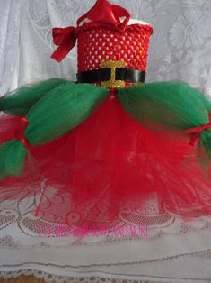 This Elf inspired tutu dress best fits infant to 18 months. The dress is handmade by me. There is only one of these dresses available so get it while you can! The santa belt can be removed . The neckline is covered in satin and a halter has been added.