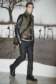 A look from the #CoachMens2015 presentation: the Military Down Bomber Vest, Black Leather Racer, Grey Heather/Military Ringer T-Shirt, Black Wool Trousers,  Feather Necklace, Zip Combat Boot and Loden Bullneck Small Manhattan Messenger