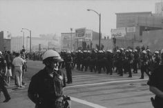 The photograph depicts a legion of police officers deploying at the 14th and Clay streets to greet the arrival of anti-draft demonstrators on a march from the University of California, Berkeley campus during Stop the Draft Week, Vietnam War protests Oct. 20, 1967.