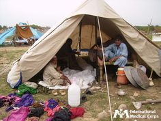 August 17: A family tries to fit under shelter after the devastating floods that hit Pakistan in 2010.    Photo: International Medical Corps Staff, Pakistan 2010