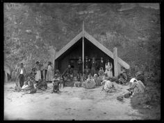Maori group and meeting house - Photograph taken by William Henry Thomas Partington, ca 1900.