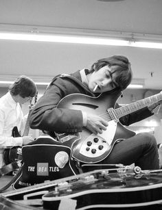John Lennon and George Harrison tuning up before a show.