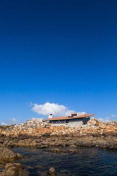 El edificio emergiendo entre las rocas. Restauración de Boa Nova Casa de Chá de Siza. Fotografía © Joao Morgado.