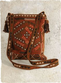 Motifs from a Banjari textile pattern our handcrocheted bag in shades of henna, raisin and copper pima; with a crochet shoulder strap, beaded tassels and snap closure.