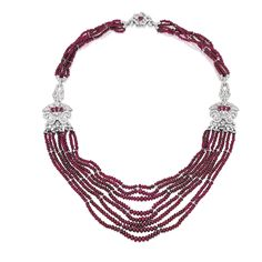 18 KARAT WHITE GOLD, RUBY BEAD, RUBY AND DIAMOND NECKLACE The multi-strand necklace composed of numerous ruby beads measuring approximately 5.8 to 3.0 mm, set with round diamonds weighing approximately 9.00 carats, the sides and clasp further set with oval-shaped rubies weighing approximately 2.10 carats, length 22½ inches.