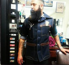 This is a dark indigo salvage 8ounce demim barbers Smock with leather trimming and blue anker buttons made by Red Wite Blue Co. it has two upprr