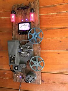 This vintage 1940's Keystone R-37 movie projector will be a cool conversation piece for your media room or man cave! The projector has been deconstructed and remounted on large piece of aged barn wood. Although the mechanism no longer runs, the projector has been brought back to life. All the old wiring has been replaced, and new switches control the red LED bulbs, the vintage panel meter and the internal LED projector light. The two reels are included as is the 8mm film. It comes with an…