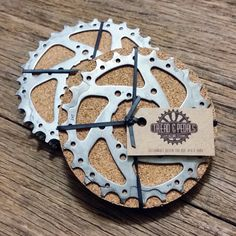 Express your passion for cycling whilst protecting your table top or bar with a set of these industrial and fun Bike Gear Coasters. These Drink Coasters have been handmade in the Tread & Pedals Upcycling Studio using recycled bicycle gears and a cork protective base. They make the perfect gift for cyclists or lovers of unique, handcrafted and eco friendly design.   Dimensions: 10cm - 12cm in diameter Other info: Comes as a set of four   As these Drink Coasters are made from recycled bike…