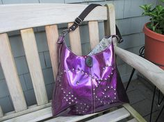 Glitter Vinyl Hobo Bag is handmade in bright purple glitter vinyl with antique brass stud accents on front.  Bag has a 2 button closure and measures 14 tall by 16 wide with a black cotton webbing shoulder strap that adjusts from 24 to 41.  Gun Metal hardware.  Fully lined with grey cotton fabric printed with horseshoes and has two large pockets.  Happy to custom make in any color combo - just convo me for details.  Please convo with any questions or concerns.  See Shop Announcement for…
