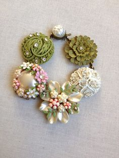 This bracelet was made with five pretty vintage earrings in shades of pink, pearl and moss green, accented with rhinestones. The bracelet