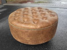 This listing is for a single upholstered ottoman artisan made in High Point NC by hand. This piece can be used as either a footstool or as a coffee table with an ottoman tray. Coffee table ottomans are inventoried and SHIPS QUICKLY within 1-3 business days of ordering via FedEx or UPS. Dimensions: 30 Round by 17.5 tall Upholstery: Diamond Tufted Material: Distressed Vegan Leather (Chestnut color) Nailhead: Brass Legs: 5 Black Pyramid