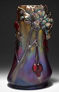 Zsolnay Pécs LAJOS MACK (1876-1963) Vase à corps tubulaire et panse renflée en céramique émaillée irisée à décor en relief de prunes et de branchages. Signé du cachet aux cinq églises. Vers 1900. H : 31 cm 05/6,5eE