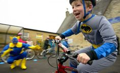 A boy enjoys the Big Pedal super hero day on his bike