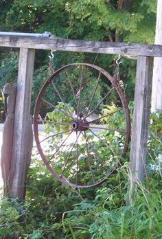Sheepscot River Primitives - We found this old metal wagon wheel at a local antique store and thought it would be great to hang from the wood frame that use to hold my business sign many years ago. The metal wheel will hold up to the winter snows better Garden Yard Ideas, Backyard Projects, Outdoor Projects, Lawn And Garden, Garden Projects, Garden Kids, Balcony Garden, Rustic Gardens, Outdoor Gardens